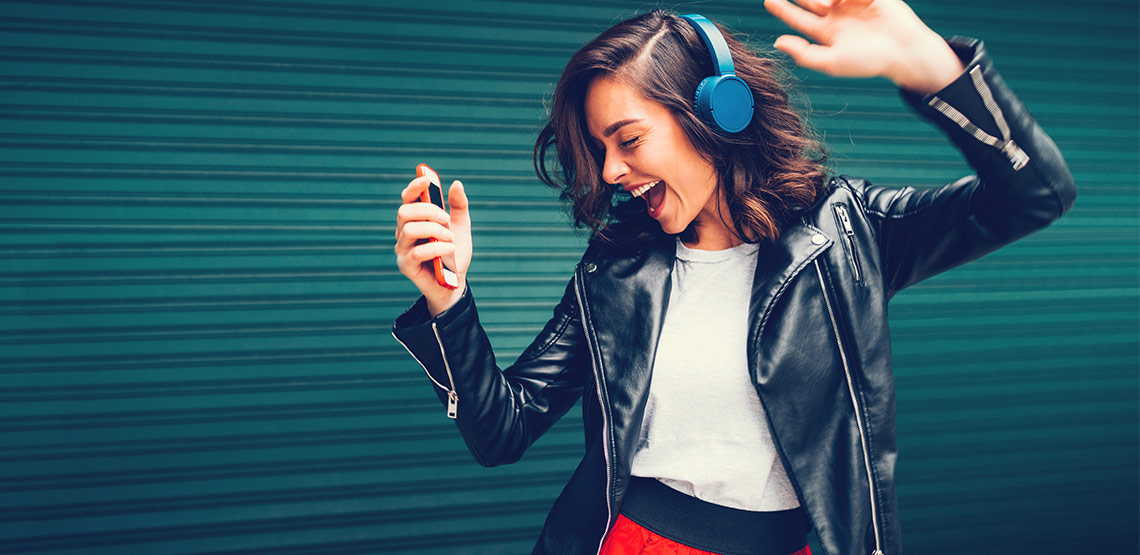 Woman wearing headphones and dancing