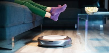 Robot vacuum cleaner going by couch