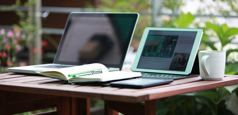 Two laptops on a desk with a notebook