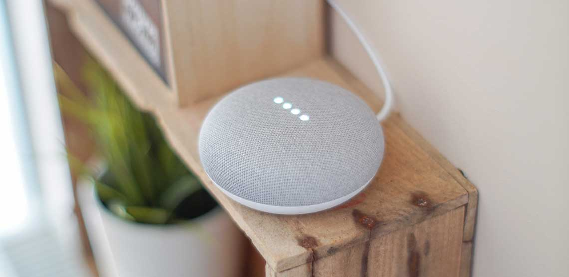 A Google Home Mini sitting on a shelf