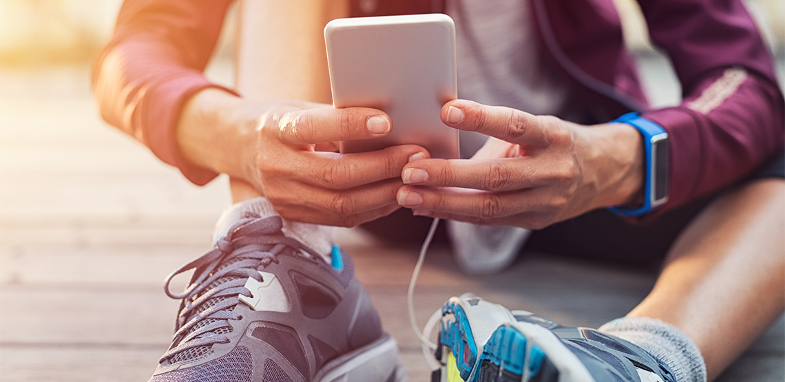 Person sitting on ground wearing running shoes and looking at phone
