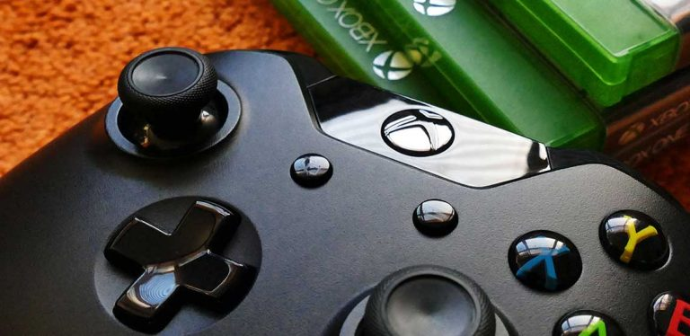 An Xbox One controller sitting beside game cases