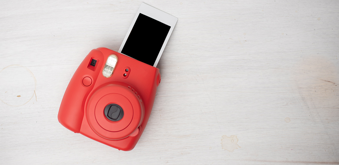 Red instant camera spitting out undeveloped photo