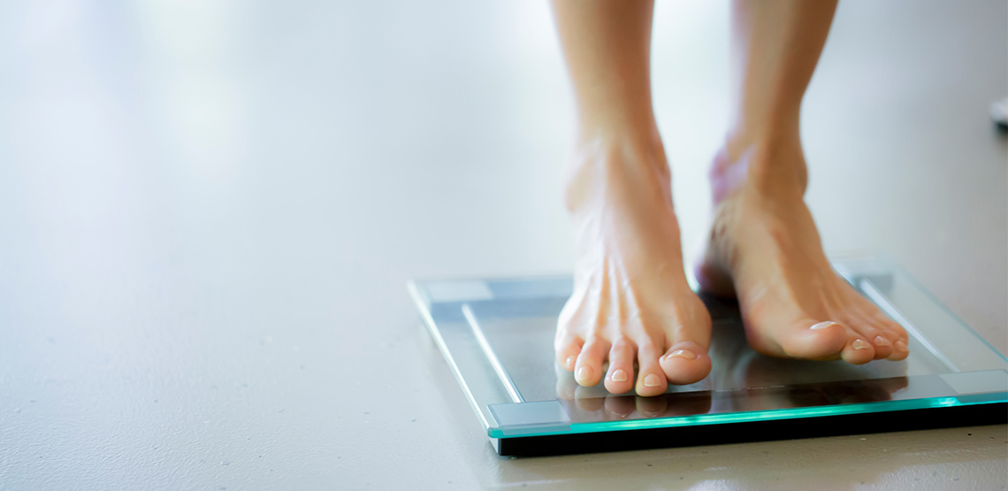 Woman standing in bare feet on a bathroom scale