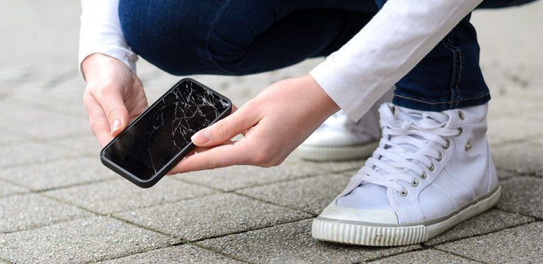 Someone picking their phone off the ground and it has a cracked screen