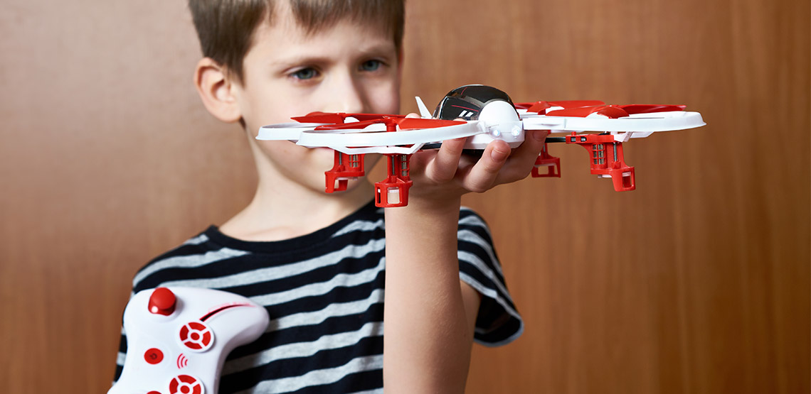 Boy holding a drone in one hand and a controller in the other
