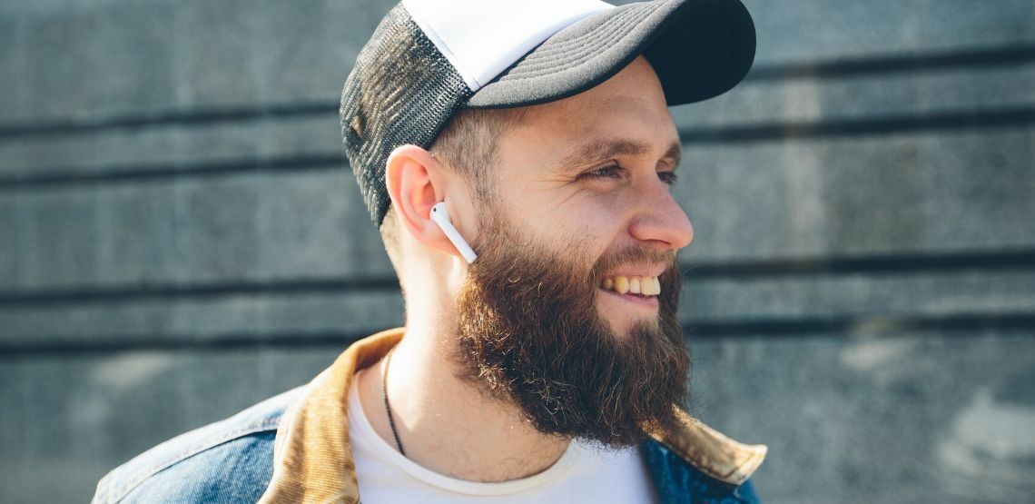 Someone wearing in-ear Bluetooth headphones.