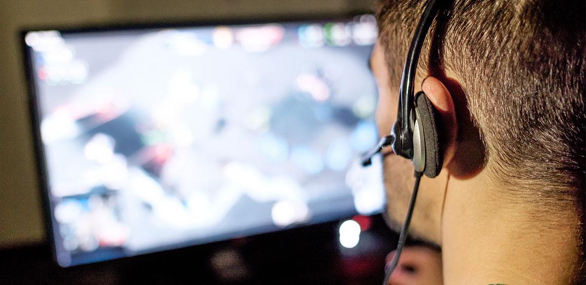 Man wearing headset playing game on computer
