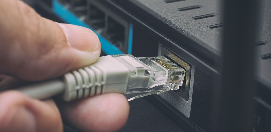 Person plugging in cable to a router