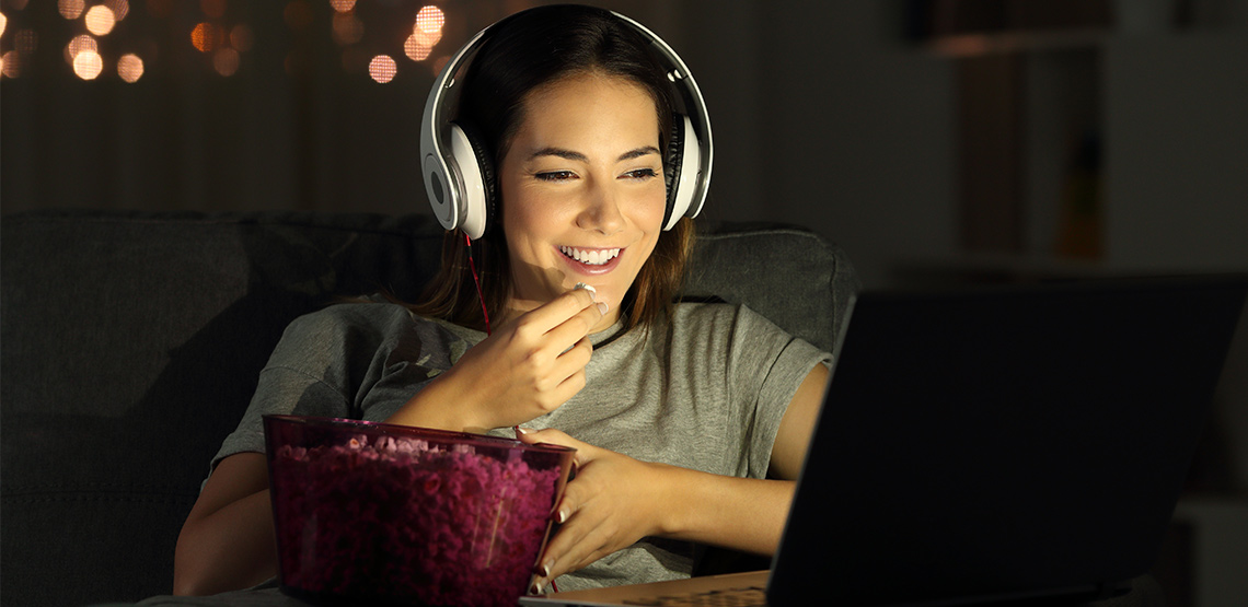 Woman eating popcorn, wearing headphones, and watching something on her laptop