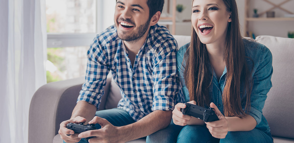 Man and woman sitting on couch with video game controllers in hand