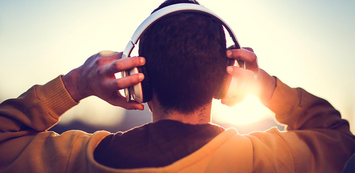 Man holding onto headphones on his head