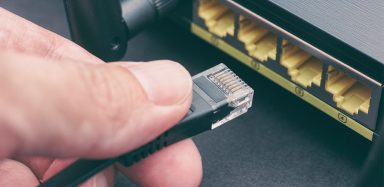 Someone plugging in cord to router