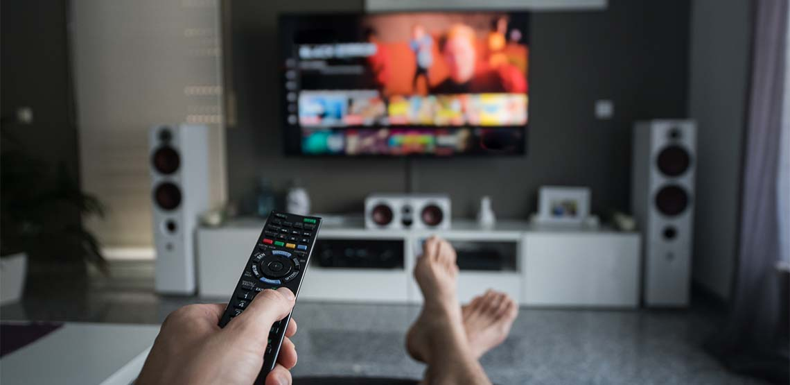 Someone pointing a remote at a TV to watch Netflix.
