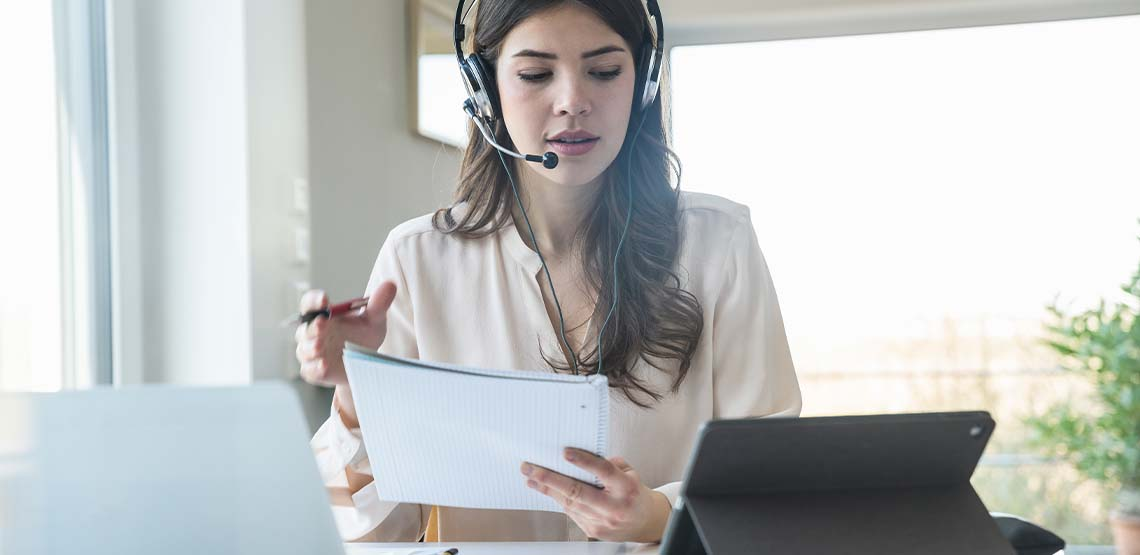 A woman with brown hair wearing a headset for a work conference call.