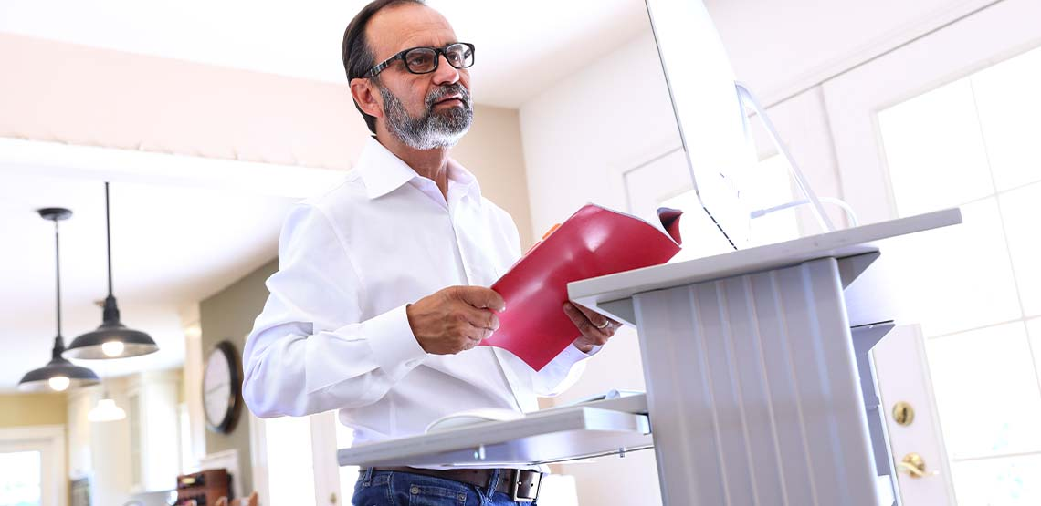 A man with glasses standing at a white standing desk in his house holding a red folder.