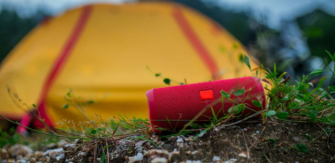 A red outdoor speaker sitting in the grass in front of a yellow tent.
