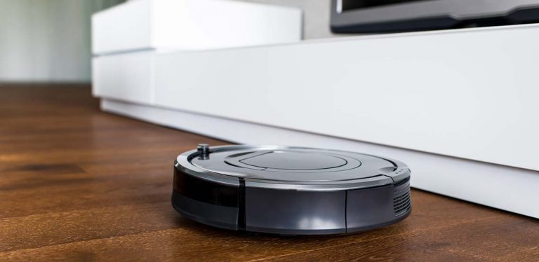 A black Roomba driving around on brown wooden floors.