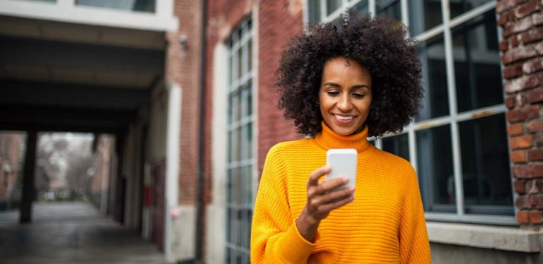 A woman wearing a yellow sweater looking at her white smartphone.