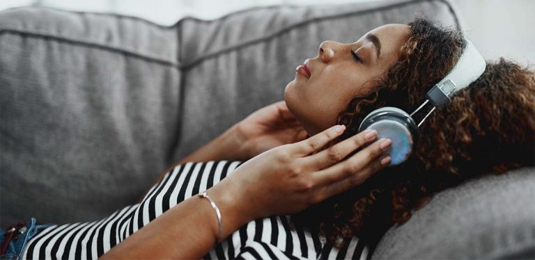 Someone laying on a grey couch wearing white over-ear, noise-cancelling headphones.