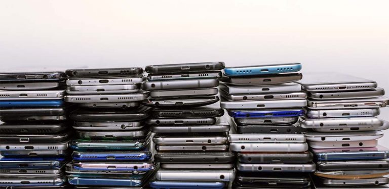 A stack of different brands of phones lined against a white background.