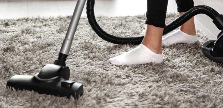 Someone vacuuming an area rug.