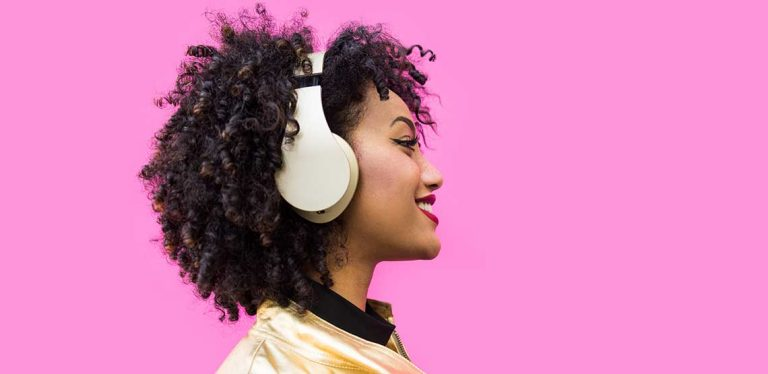 A woman standing in front of a pink wall, wearing wireless headphones.