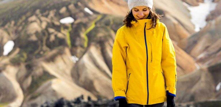 A person wearing a yellow heated coat outside.