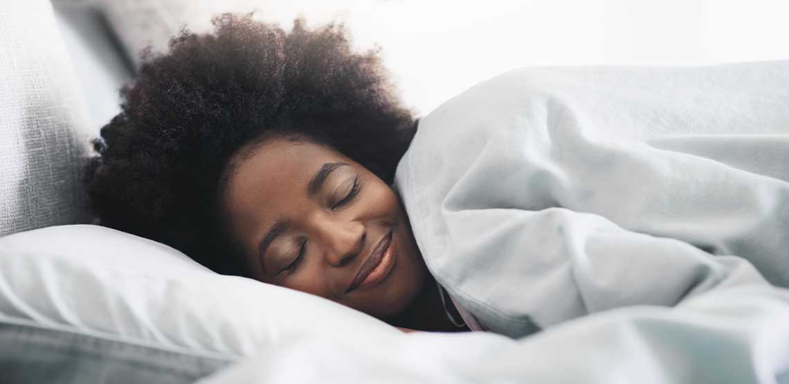 A person sleeping in bed with a duvet over them.