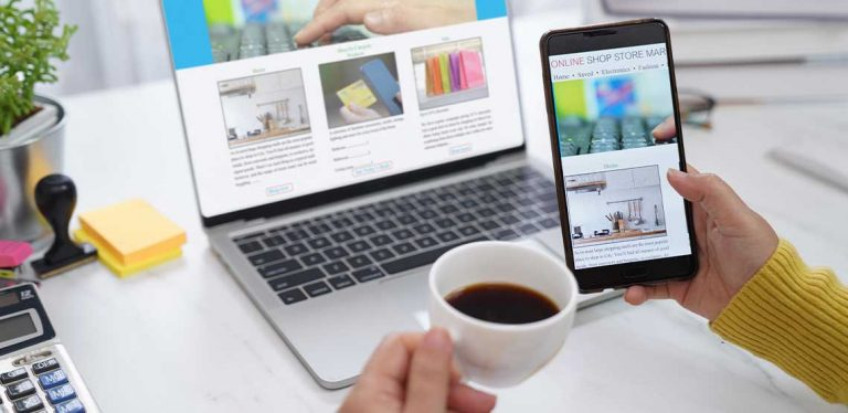 A person holding a phone and a cup of coffee with an open laptop in the background showing a business website.