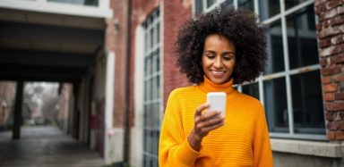 A woman in a yellow sweater holding a cell phone.